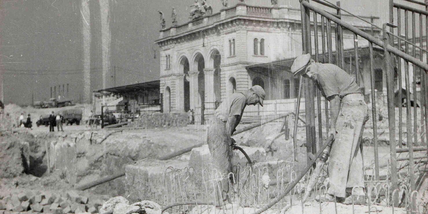 Arbeiter vor einem kriegbeschädigten Bahnhofsgebäude